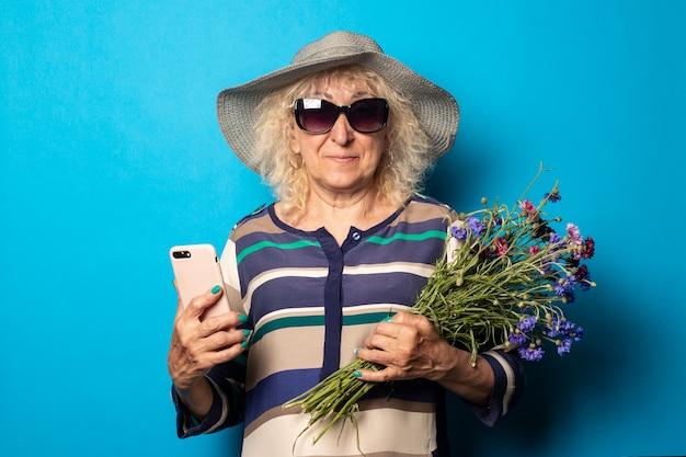 Glimlachende oude vrouw die met een boeket van bloemen telefoon houdt