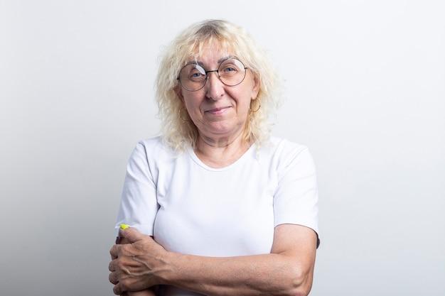 Glimlachende oude vrouw in een wit t-shirt met een bril op een lichte achtergrond.