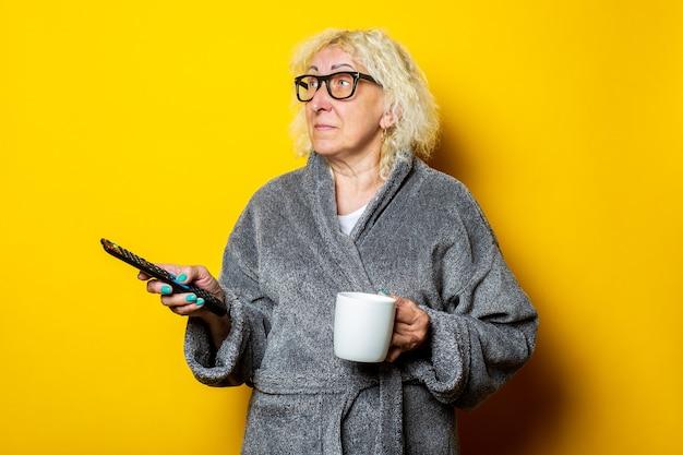 Glimlachende oude vrouw in grijze badjas met een afstandsbediening en een kopje koffie op zoek naar de kant