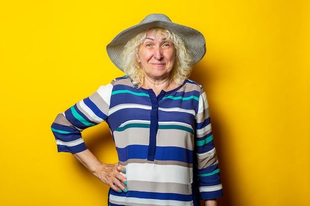Glimlachende oude vrouw in jurk en hoed houdt haar hand in de taille op een gele ondergrond