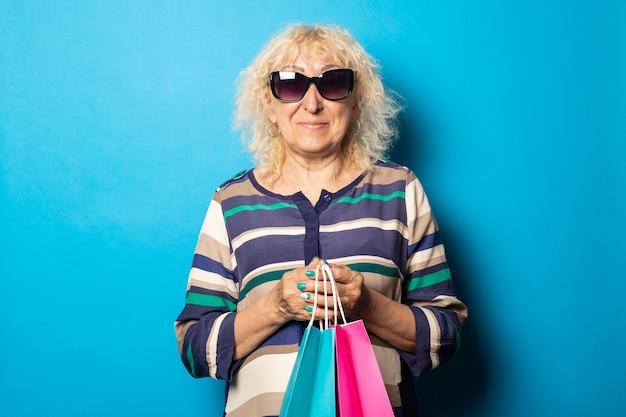 Glimlachende oude vrouw met boodschappentassen op blauwe muur.