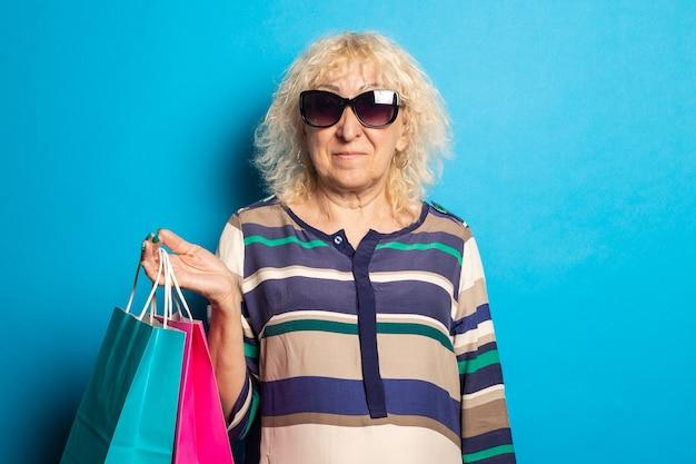 Glimlachende oude vrouw met boodschappentassen op blauwe ondergrond