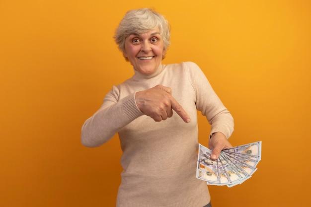 Glimlachende oude vrouw met een romige coltrui die vasthoudt en wijst naar geld geïsoleerd op een oranje muur met kopieerruimte