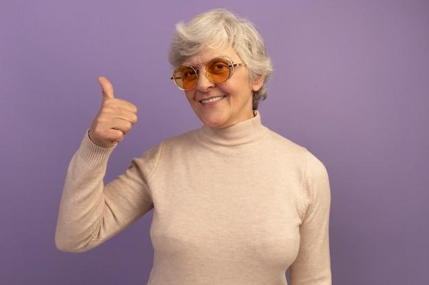 Glimlachende oude vrouw met een romige coltrui en een zonnebril die naar de voorkant kijkt en duim omhoog laat zien op een paarse muur