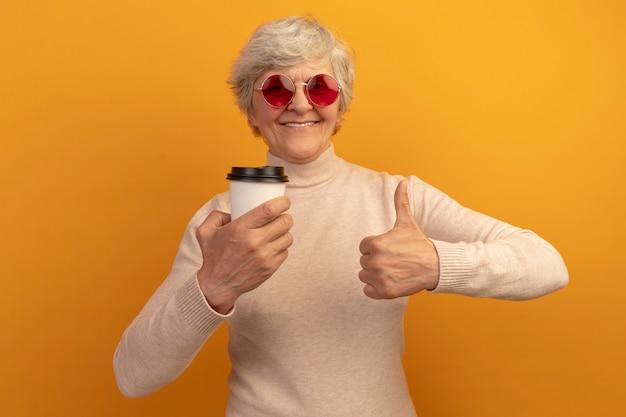 Glimlachende oude vrouw met een romige coltrui en een zonnebril met een plastic kopje koffie met een duim omhoog geïsoleerd op een oranje muur