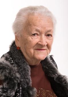 Glimlachende oude vrouw op een wit