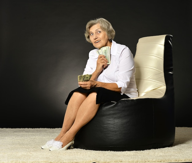 Glimlachende oude vrouw zittend op een donkere achtergrond