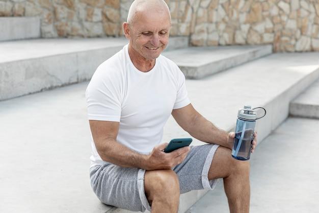 Glimlachende oudere mens die zijn telefoon cheking