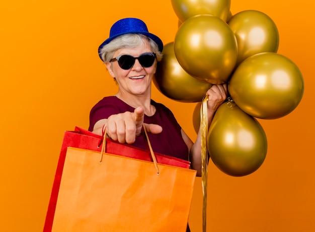 Glimlachende oudere vrouw in zonnebril met feestmuts houdt helium ballonnen en papieren boodschappentassen wijzen geïsoleerd op oranje muur met kopie ruimte