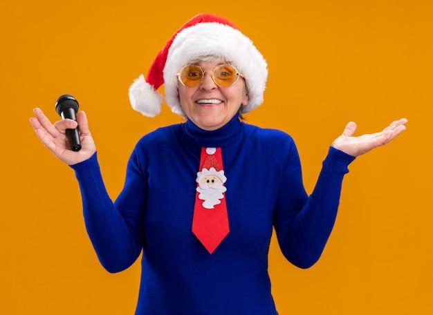 Glimlachende oudere vrouw in zonnebril met kerstmuts en kerststropdas die microfoon vasthoudt en hand open houdt geïsoleerd op oranje muur met kopieerruimte