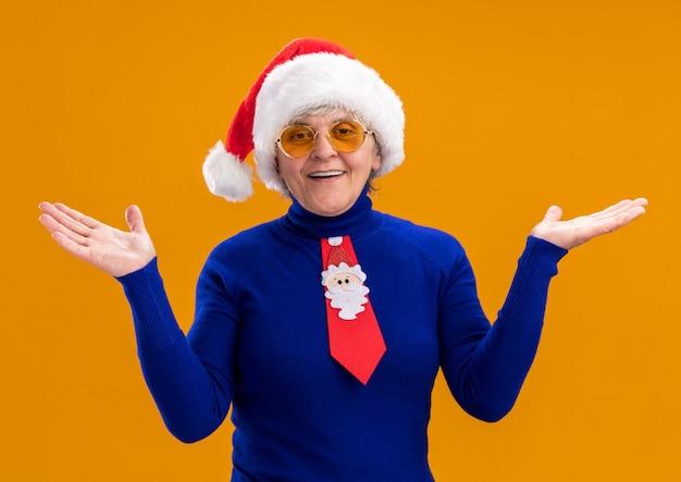 Glimlachende oudere vrouw in zonnebril met kerstmuts en santa stropdas hand in hand open geïsoleerd op een oranje achtergrond met kopie ruimte