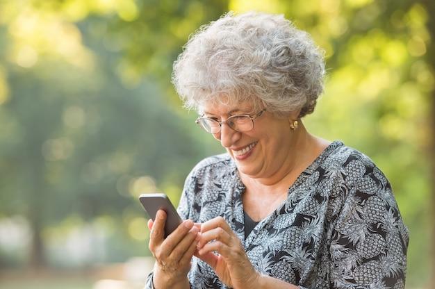 Glimlachende oudere vrouw met behulp van een smartphone