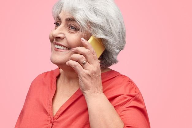 Glimlachende oudere vrouw praten over de telefoon
