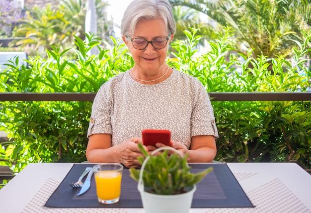 Glimlachende oudere vrouw zittend aan een cafétafel met een verse jus d'orange ervoor