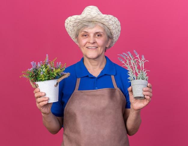 Glimlachende oudere vrouwelijke tuinman die een tuinhoed draagt en bloempotten vasthoudt
