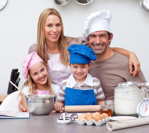 Glimlachende ouders die kinderen helpen die in de keuken bakken