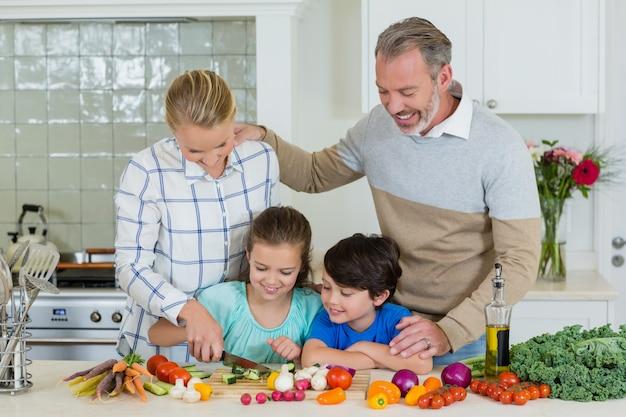 Glimlachende ouders en kinderen die groente in keuken hakken