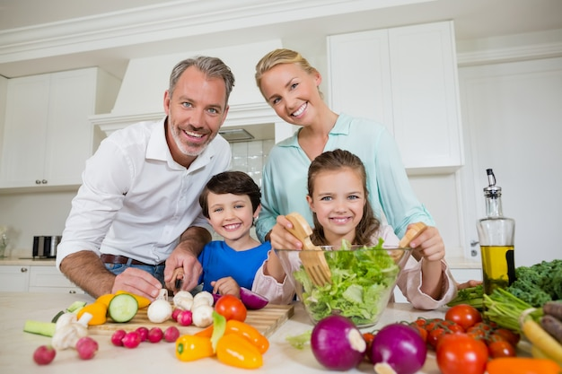 Glimlachende ouders en kinderen die plantaardige salade in keuken voorbereiden