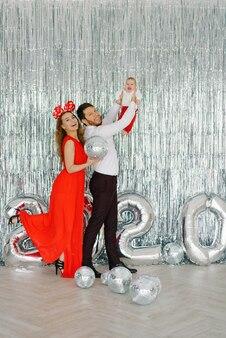 Glimlachende ouders houden hun kind in hun armen en zien het oude jaar af, ontmoeten het nieuwe jaar