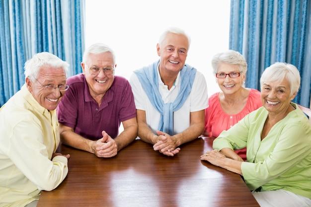 Glimlachende oudsten die bij lijst zitten