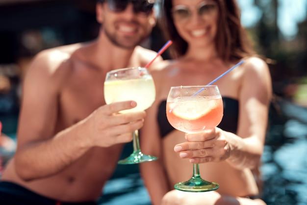 Glimlachende paar het drinken cocktails bij poolside