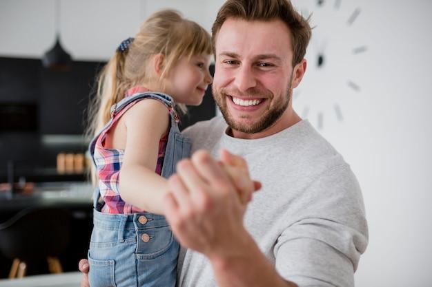 Glimlachende papa die met dochter danst
