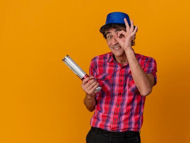 Glimlachende partijman van middelbare leeftijd die partijhoed draagt die front met confettikanon kijkt die blikgebaar doet geïsoleerd op oranje muur met exemplaarruimte