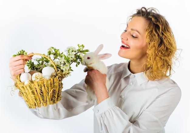 Glimlachende pasen-vrouw met wit konijn en mand met eieren.
