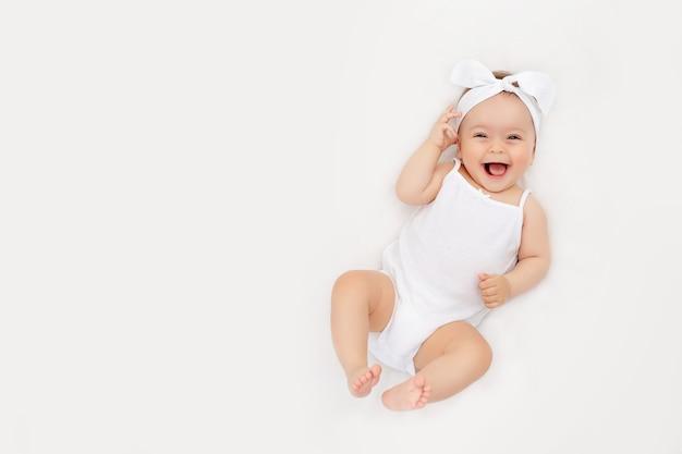 Glimlachende pasgeboren baby op een wit bed thuis, het concept van een gelukkige, gezonde baby