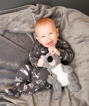 Glimlachende pasgeboren babyjongen zit met panda speelgoed op grijze deken