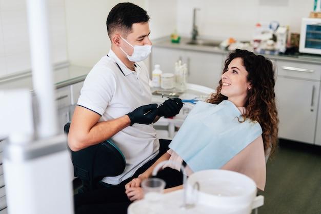 Glimlachende patiënt op tandartskantoor na controle