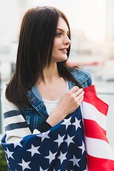 Glimlachende patriottische vrouw die in de vlag van de vs wordt verpakt