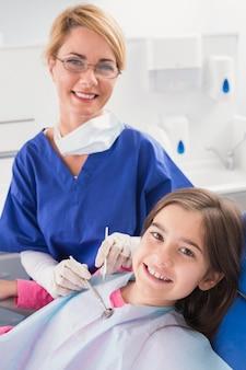 Glimlachende pediatrische tandarts met een gelukkige jonge patiënt
