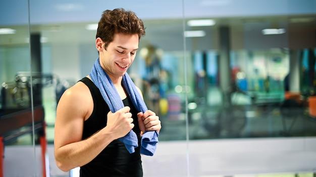 Glimlachende persoonlijke trainer in de gymnastiek met handdoek om zijn hals