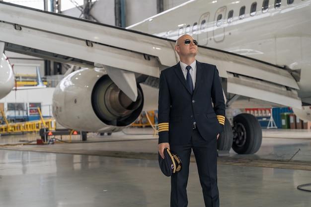 Glimlachende piloot in uniform en pilotenzonnebril