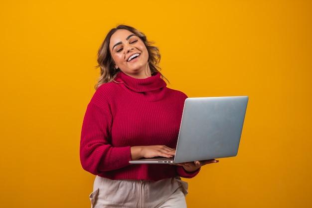 Glimlachende plus size vrouw met een laptop op gele achtergrond.
