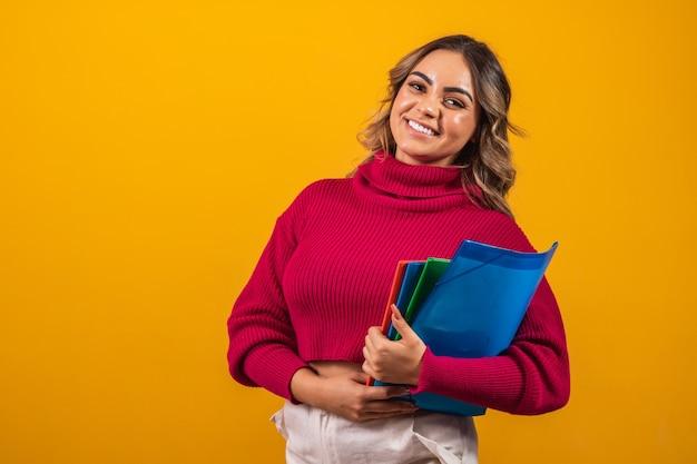 Glimlachende plus size vrouw student met schoolboeken in handen op gele achtergrond.