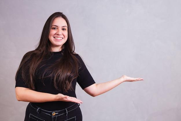 Glimlachende plus size vrouw wijzend naar de zijkant met ruimte voor tekst.