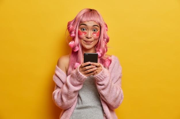 Glimlachende positieve aziatische vrouw houdt mobiele telefoon in handen, controleert e-mailbox, ziet er graag uit, heeft roze haren, draagt rollen