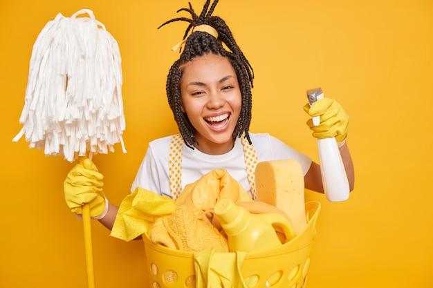 Glimlachende positieve huisvrouw met dreadlocks houdt dweil vast