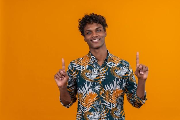 Glimlachende positieve jonge knappe donkerhuidige man met krullend haar in bladeren bedrukt overhemd wijzend met wijsvingers omhoog terwijl het kijken naar camera op een oranje achtergrond