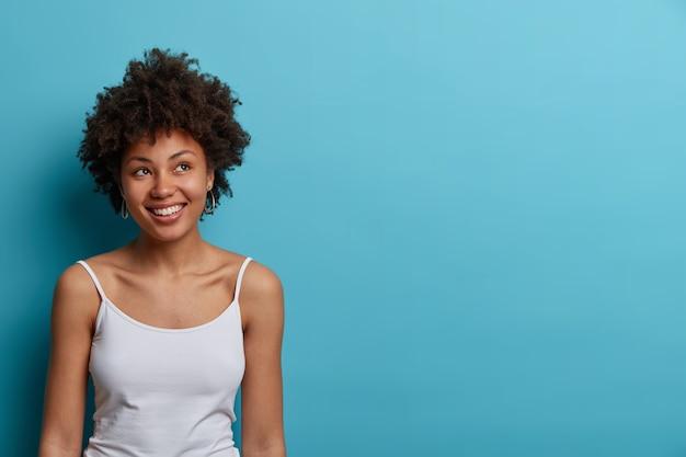 Glimlachende positieve jonge vrouw met afro haar kijkt weg met dromerige uitdrukking, denkt over een goede toekomst, heeft brede glimlach, draagt casual t-shirt, vormt tegen blauwe muur, lege ruimte voor tekst