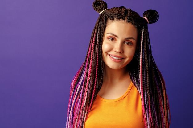 Glimlachende positieve jonge vrouw met kleurrijke afrikaanse vlechten