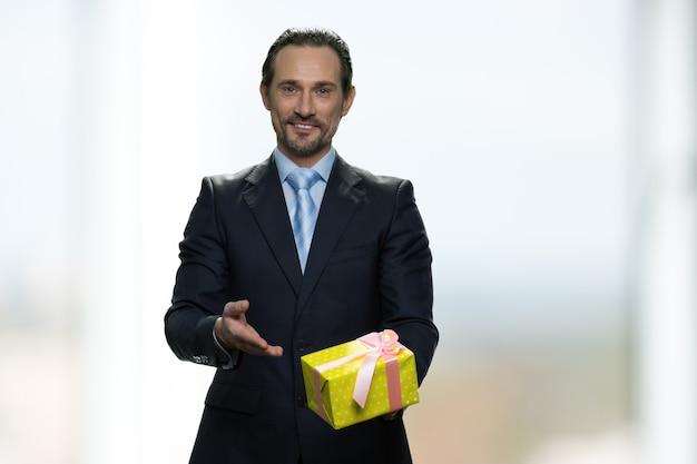 Glimlachende positieve zakenman presenteert gele geschenkdoos. heldere onscherpe achtergrond.
