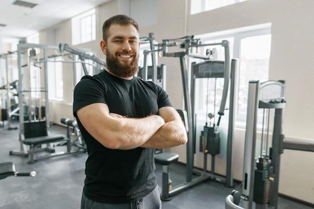 Glimlachende positieve zekere mannelijke persoonlijke instructeur