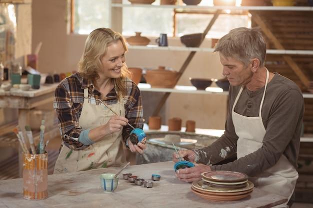 Glimlachende pottenbakkers die op kom in aardewerkworkshop schilderen