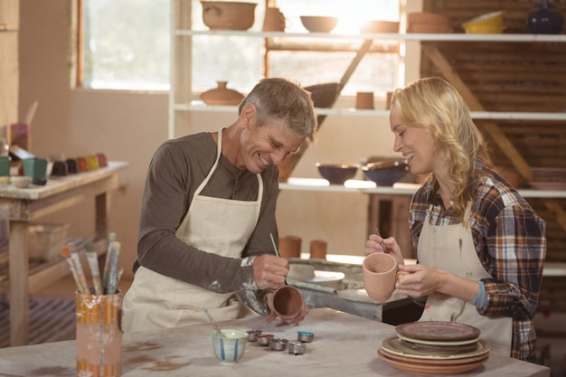 Glimlachende pottenbakkers die op kop schilderen