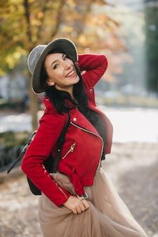 Glimlachende prachtige dame met zwart haar genieten van herfstdag