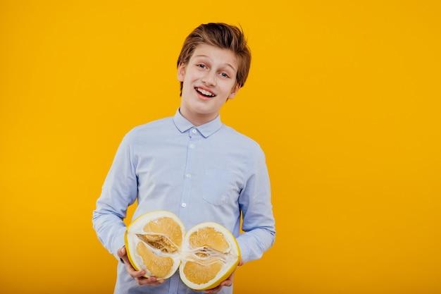 Glimlachende preteen jongen met pompelmoes in de hand fruit, in het blauwe shirt, geïsoleerd op gele muur