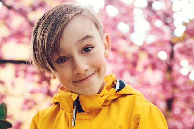 Glimlachende preteenjongen die aan camera kijkt. gezicht emoties, expressie. leuke jongen die stijlvolle outfit draagt in het voorjaar. knappe jongen die in de lentepark loopt. gelukkige jongen die zich voordeed op sakura bloeiende achtergrond.